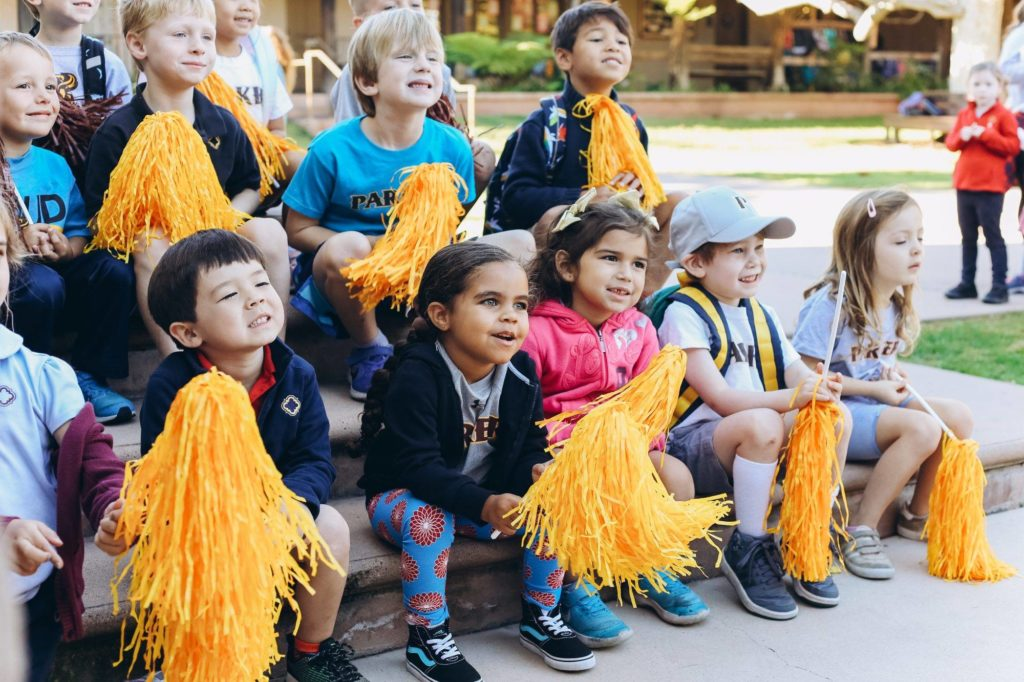 junior kindergarteners laugh as they shake Parker spirit pompoms